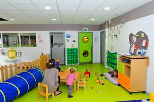 Une salle de jeux décorée avec 3 enfants, une professionnelle et des jouets sur le sol vert