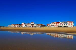 Le front de mer au soleil couchant qui se reflète dans le miroir d'eau du sable