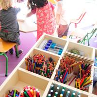 Casiers à crayons en premier plan et enfants dans une classe en second plan