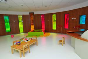 salle dédiée au Relais Assistantes Maternelles dont la particularité sont ses fenêtres colorées comme des vitraux sur un mur rond