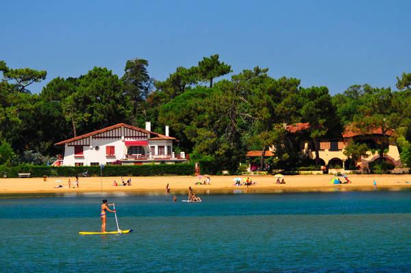 Deux maisons basco-landaises au bord du lac, dans les pins, avec quelques vacanciers sur la plage et une femme en stand up paddle au premier plan