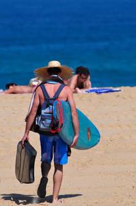 Un surfeur avec un chapeau de paille, une planche de surf et une planche de bodyboard sous chaque bras marche sur le sable en direction de la mer