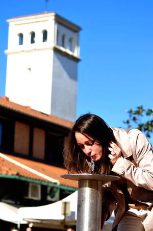 Jeune femme brune aux cheveux longs boit à la fontaine de la place Pasteur en centre-ville avec en fond l'église de la Sainte Trinité d'Hossegor