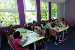 Les enfants déjeunent à la cantine de Soorts : murs violets et tables vertes