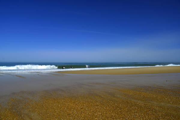 L'eau et le ciel bleu azur et des surfeurs prenant de petites vagues