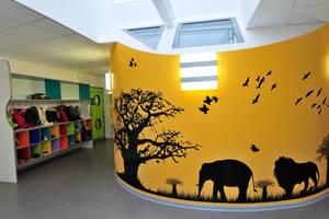 Le hall d'entrée de la crèche avec une fresque des animaux de la savane (éléphant et lion) peinte en jaune et les casiers des enfants sur la gauche